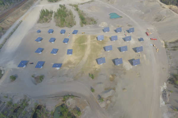 Two fields of solar trackers in a gravel pit