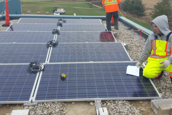 Solar panels being installed on gravel roof