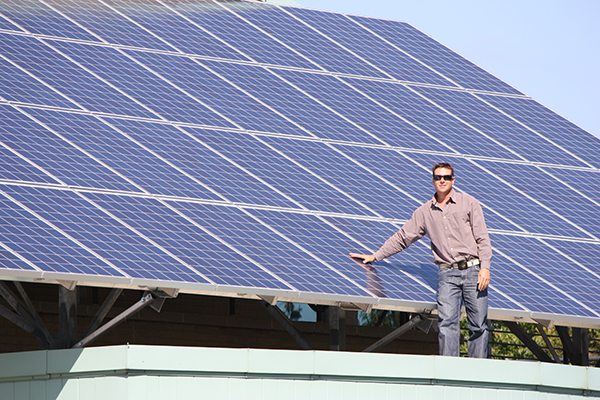 Man standing in front of solar panels
